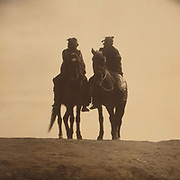 Two native American men mounted on horses, in silhouette, gazing off into the distance, c1904. Photograph by Edward Curtis (1868-1952 ).