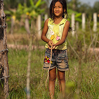 A young girl fishing in the rice fields along the road.