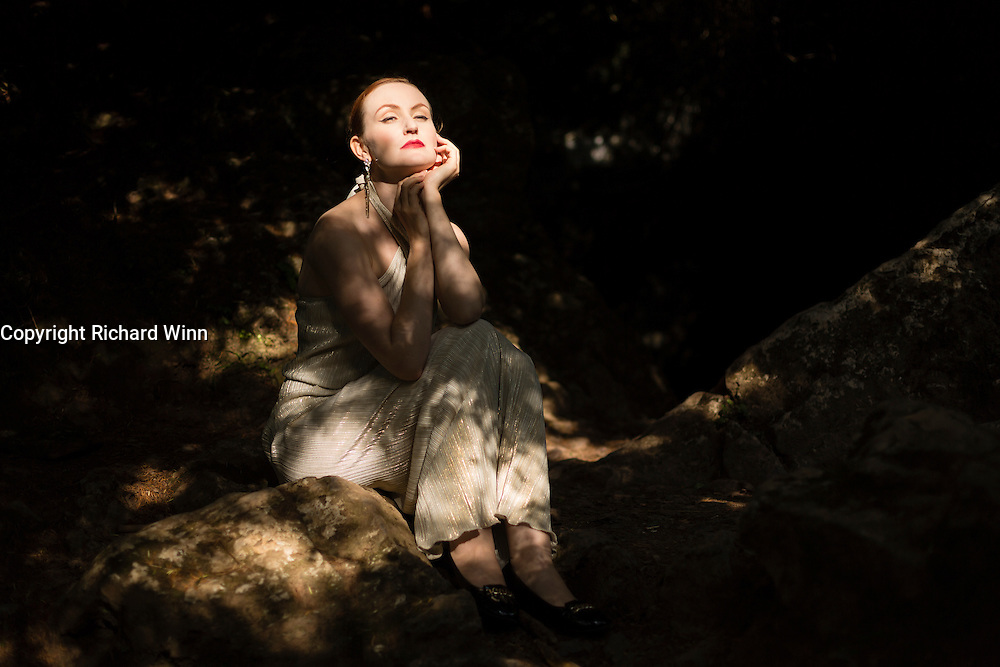 Woman in long dress, lit by light filtering through the trees of woodland in Cheddar Gorge.