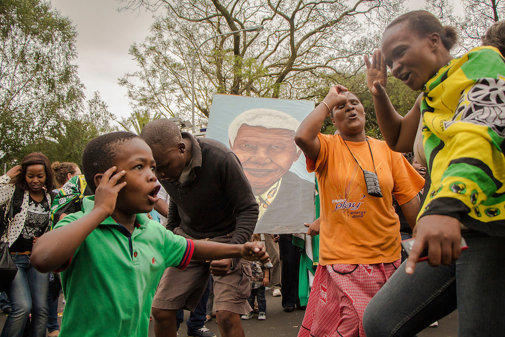 People gathered outside Nelson Mandela's house in Houghton, sing revolutionary songs and do the military salute as a tribute to the former late President, on Friday. Dec.6 2013.