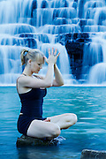 Woman sits in meditation by a waterfall while balancing on a rock.