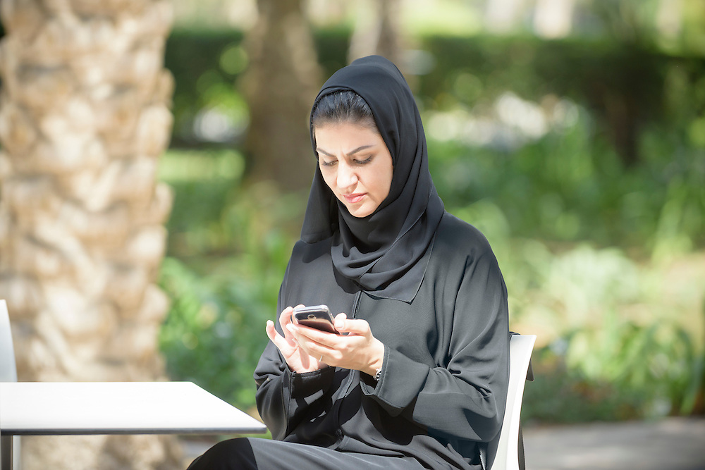 Candid portrait of Emirati Arab business woman texting on mobile smartphone. Middle Eastern businesswoman dressed in traditional black abaya is sitting outdoors and is using modern mobile communication technology for wireless social networking and browsing. Dubai, United Arab Emirates.