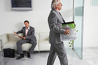Business man carrying box past a man reading newspaper in office hallway