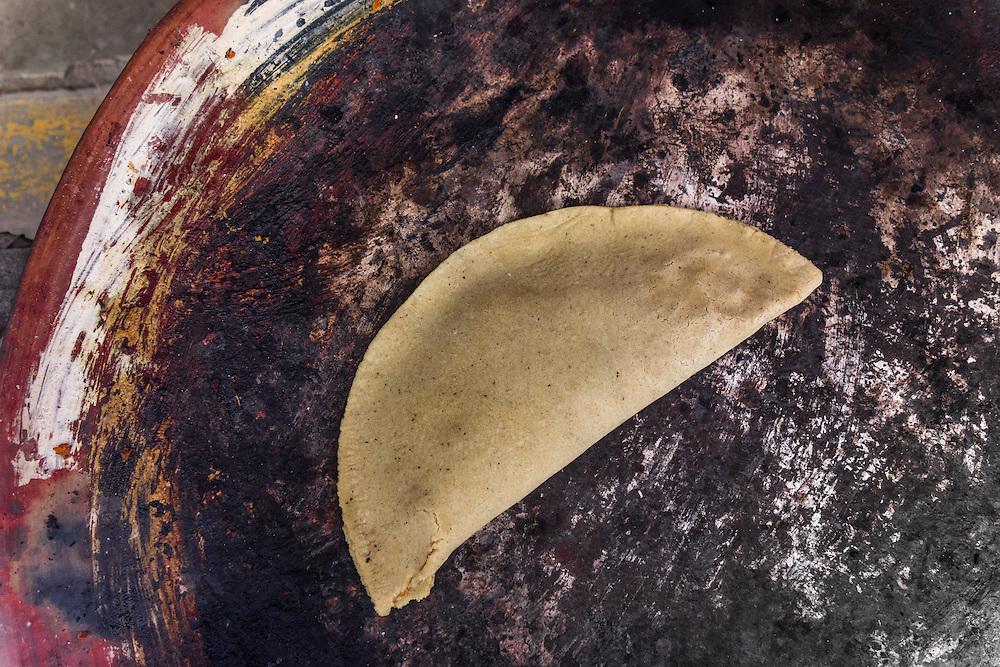 A classic Street antojito from the streets of Oaxaca, filled with mole coloradito, herbs and shredded pork or chicken. Un Antojito clasico de Oaxaca relleno de mole coloradito, hierbas y pollo o puerco desmenuzado.