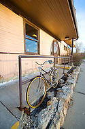 A bike is locked up outside a suburban commuter station.