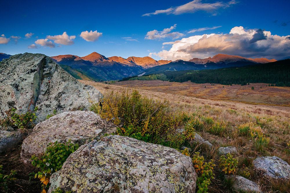 Disapating thunderstorm clouds over the Sawatch Range in Colorado highlight lichen covered boulders.