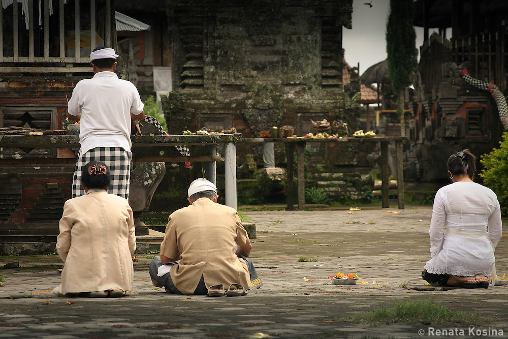 Group of local Balinese sit in a prayer in Ulun Danu Batur temple. Named after a goddess that rules the water supply, this pura is the second most significant in Bali and has over 100 shrines.