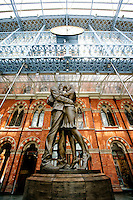 The Meeting Place bronze statue and  The Station Clock, The St. Pancras Railway Station, London, England.