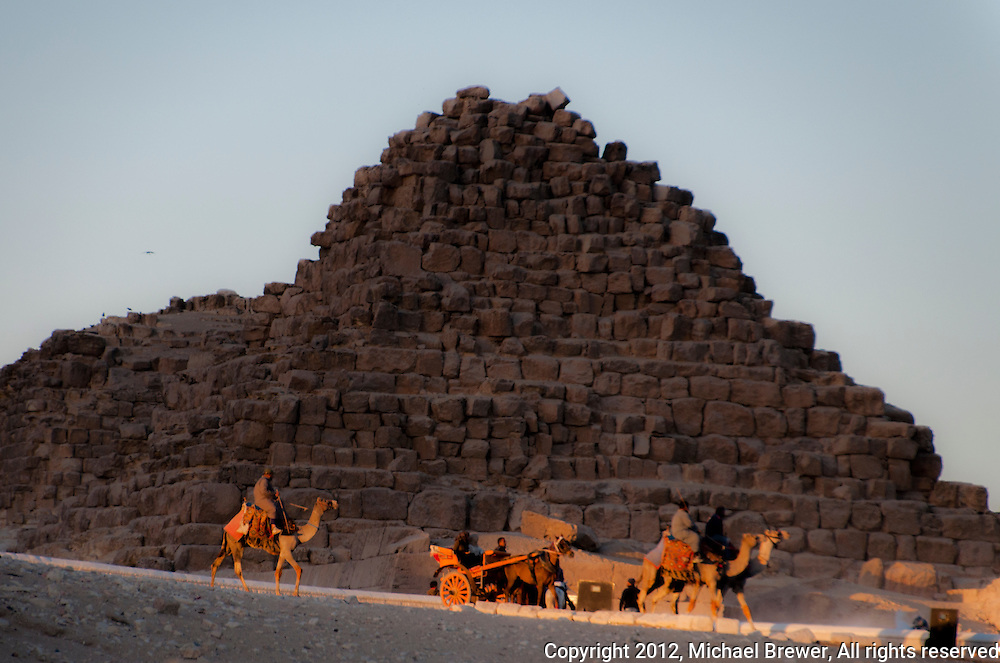 Camels and wagons in front of a ruined pyramid in Giza, Egypt.