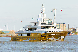 © Licensed to London News Pictures. 17/09/2019. London, UK. Gold wrapped, 175 feet long superyacht, Bellami.com arrives in London passing the Cable Car on the River Thames before mooring in East India Dock. It took 13 days and 600sqm of gold chrome vinyl wrap to cover the superyacht formally known as 'Kinta' at the Port of Viareggio in Italy this year and is the largest chrome yacht wrap done fully in the water and possibly the largest chrome wrap ever. As Bellami.com arrived, it was noticed that some of the chrome wrap was already damaged and missing. Photo credit: Vickie Flores/LNP