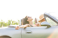 Happy woman enjoying road trip in convertible with friend