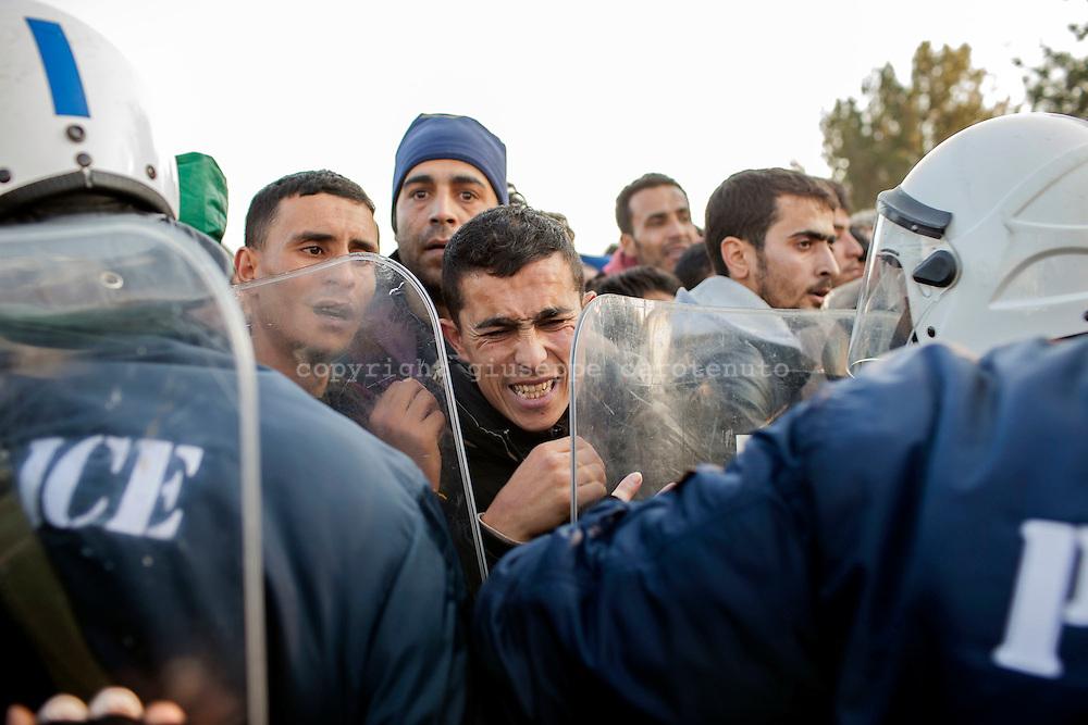 03 December 2015, Greece, Idomeni - Migrants and refugees wait to cross the Greek-Macedonian border near the village of Idomeni, Greece - Migrants and refugees push against the Greek police to cross the border.