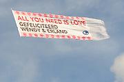 Wendy van Dijk en Erland Galjaard zijn getrouwd op Ibiza in het Agroturismo Atzaró . Agroturismo Atzaró bevindt zich in een sinaasappelboomgaard op het platteland van Ibiza. Dit mooie, landelijke hotel beschikt over een klein buitenzwembad en een kleine spa. <br /> <br /> Op de foto: <br />  Een vliegtuig met tekst vliegt over de bruiloft heen