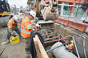 Workers lower equipment into a trench being excavated at 4th and Freelon, where two sewer lines are being installed.