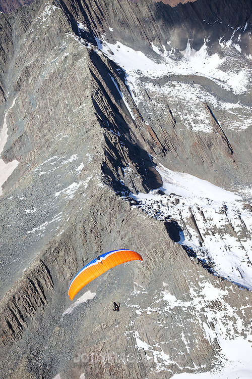 Paraglider soars over the high himalayan mountains above snow and ice