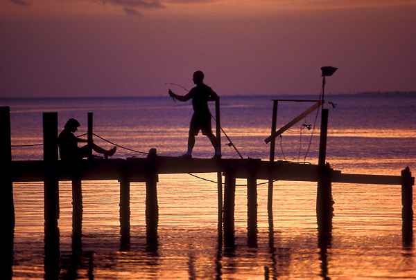 Stock photo of fishing off a pier at sunset.