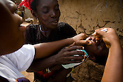 A health worker vaccinates a child against polio in the village of Gidan-Turu, northern Ghana on Thursday March 26, 2009.