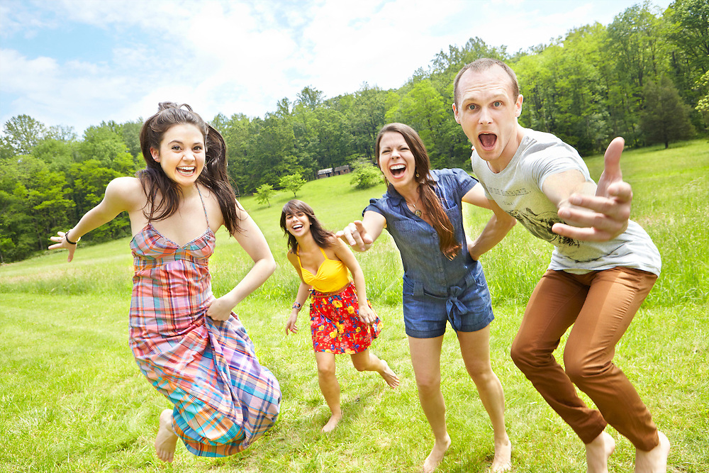 Lifestyle image of young group jumping and playing in a field during Spring