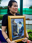 24 OCTOBER 2017 - BANGKOK, THAILAND: A woman mourning the Late King walks along Atsadang Rd, near the cremation site, in Bangkok. People started camping out along Atsadang Road in Bangkok near the royal cremation site on Monday. The gates won't open until Wednesday morning and the cremation isn't until Thursday night, so most people will sleep outside, on sidewalks and footpaths for three nights. Hundreds of thousands of people are expected to try to get into Sanam Luang, the site of the cremation of Bhumibol Adulyadej, the Late King of Thailand, but the site will only hold about 60,000 people. The Thai government has built replica crematoriums around Bangkok to accommodate the overflow crowds.        PHOTO BY JACK KURTZ