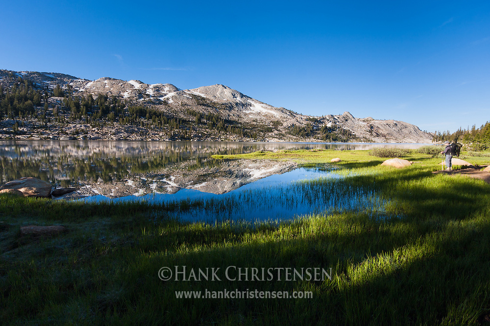A backpacker looks across Emigrant Lake in the early morning