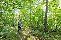 A woman and her daughter run on a forest trail at Barker's Farm in Stratham, New Hampshire.