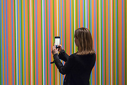 © Licensed to London News Pictures. 01/03/2019. LONDON, UK. A staff member views ''Midi'', 1983, by Bridget Riley, (Est. £1,200,000 - 1,800,000).  Preview of Sotheby's Contemporary Art Sale in their New Bond Street galleries.  Works by artists including Tracey Emin, Jenny Saville, Jean-Michel Basquiat and Andy Warhol will be offered for auction on 5 March 2019.  Photo credit: Stephen Chung/LNP