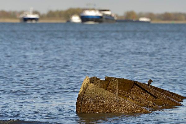 Nederland, Nijmegen, 13-11-2015De waterstand in de rivier de Waal is laag. Er is een extreem lange droogteperiode, periode van droogte in het stroomgebied van de Rijn. Binnenvaartschepen nemen minder lading, vracht in en moeten goed in de vaargeul blijven. Hierdoor is het drukker op de rivier. Een gezonken houten zeilboot komt tevoorschijn.Foto: Flip Franssen/HH
