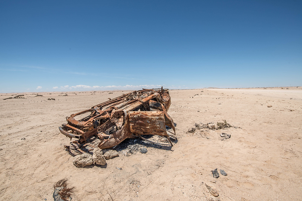An abandoned, rusted car frame sits in the Namib desert, located in Namibia, Africa.