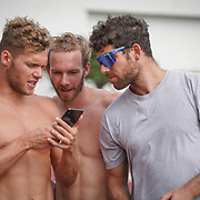 JANUARY 24, 2019--MIAMI, FLORIDA,<br /> Foto left; Kevin Mayer, left, a world record holder in decathlon from France, Benjamin Hougardy, an athlete from Belgium, and Thomas Mayer, Kevin's brother and manager, look at videos of each other shot during a work out in a track and field facility on the University of Miami.<br /> (Photo by Angel Valentin)
