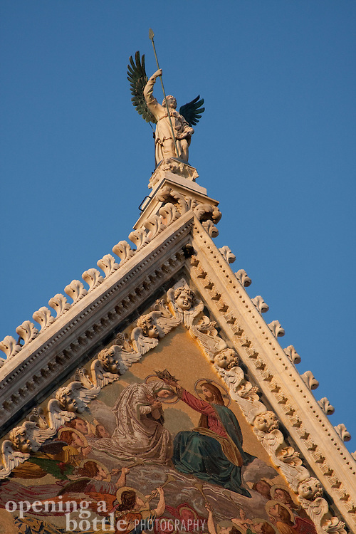 An angel crowns the facade of the spectacular duomo in Siena, Tuscany, Italy.