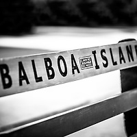 Balboa Island Bench picture. Balboa Island is a popular area of Newport Beach in Orange County California. The wooden parkbench has Balboa Island engraved in it. Photo is black and white.