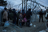 A syrian family stands at the Greek border crossing to Macedonia as they wait for their travel documents to be approved by Macedonian police on December 1, 2015.
