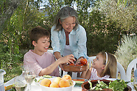 Senior woman serving fruit to children (6-11) in garden