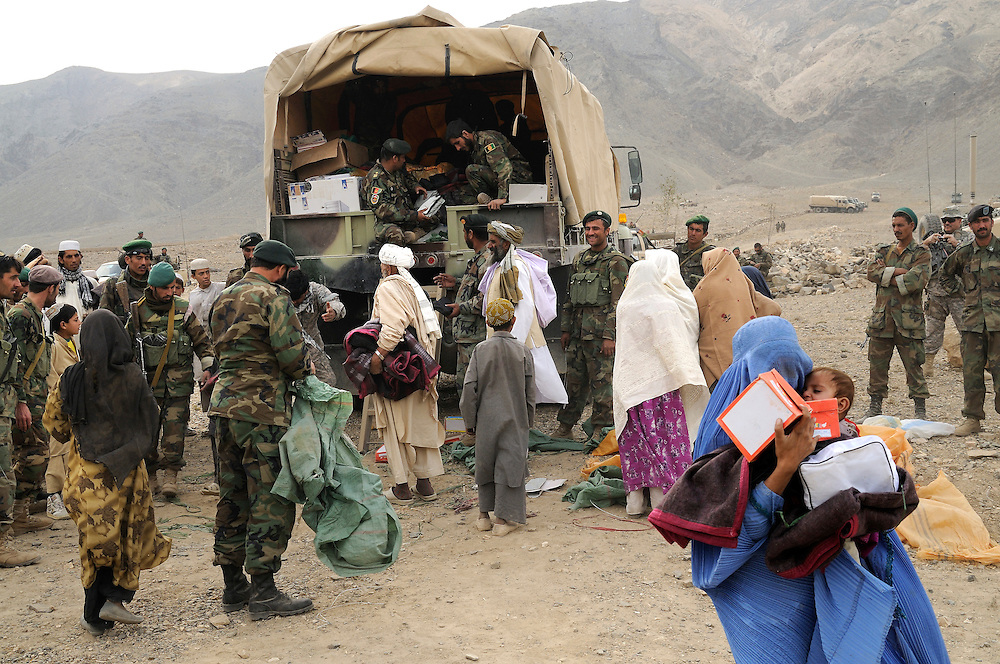 "ANA soldiers from 3rd Brigade, 201st Corps, distribute free humanitarian assistance to villagers during an operation in Tagab Valley...US Marine Colonel Jeff Haynes said the battle plan, ""The creeping barrage of goodness,"" to win the hearts and minds of the Tagab Valley includes: a paved road, wells, radio stations, solar power, humanitarian aid, and medical outreach.  Agricultural development teaching how to package goods, and pruning techniques to increase crop yields.  Saffron cultivation started too, as a replacement to poppy.  More projects like schools and police checkpoints will follow as resources allow..."