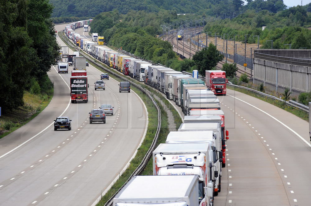 © Licensed to London News Pictures. 28/07/2015<br /> Operation stack lorries between J8 and J9 for Ashford on the M20. Highspeed Javelin train in pic.<br /> Operation stack is back on the M20 in Kent.<br /> Just days after Operation Stack was taken off the M20, it was brought back in the early hours of this morning.<br /> The authorities are blaming a heavy volume of traffic heading towards the Port of Dover and Eurotunnel and the continued disruption in Calais.<br /> The coast-bound carriageway between junctions 8 and 9 is closed to allow lorries to park, but the slip roads at junctions 9, 10 and 12 and 13 have also been shut. <br /> <br /> (Byline:Grant Falvey/LNP)