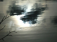 reflected clouds and sunlight in a pond water in grey color with smooth pastel tone