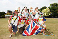 Photo by Andrew Tobin/Tobinators Ltd - 07710 761829 - Top row L-R Rachel Cross, Emma Watson, Aimi Bresler and Michelle Berry, lower row L-R Jim Collins, Dan Cross, Rob Bresler and Ian Ashmead pose for a photo during the World Peashooting Championships held at Witcham, Cambridgeshire, UK on 13th July 2013. Run in conjunction with the village fair, the Championships have been held in Witcham since 1971 when they were started by a Mr Tyson, the village schoolmaster, in order to raise funds for the village hall.Competitors come from as far afield as the USA and New Zealand to attempt to win the event. The latest technology is often used, including laser sights and titanium and carbon fibre peashooters. All peashooters must conform to strict length rules, not exceeding 12 inches, and have to hit a target 12 feet away. Shooting 5 peas at a plasticine target attached to a hay bale, the highest scorers move through the initial rounds to a knockout competition, followed by a sudden death 10-pea shootout.