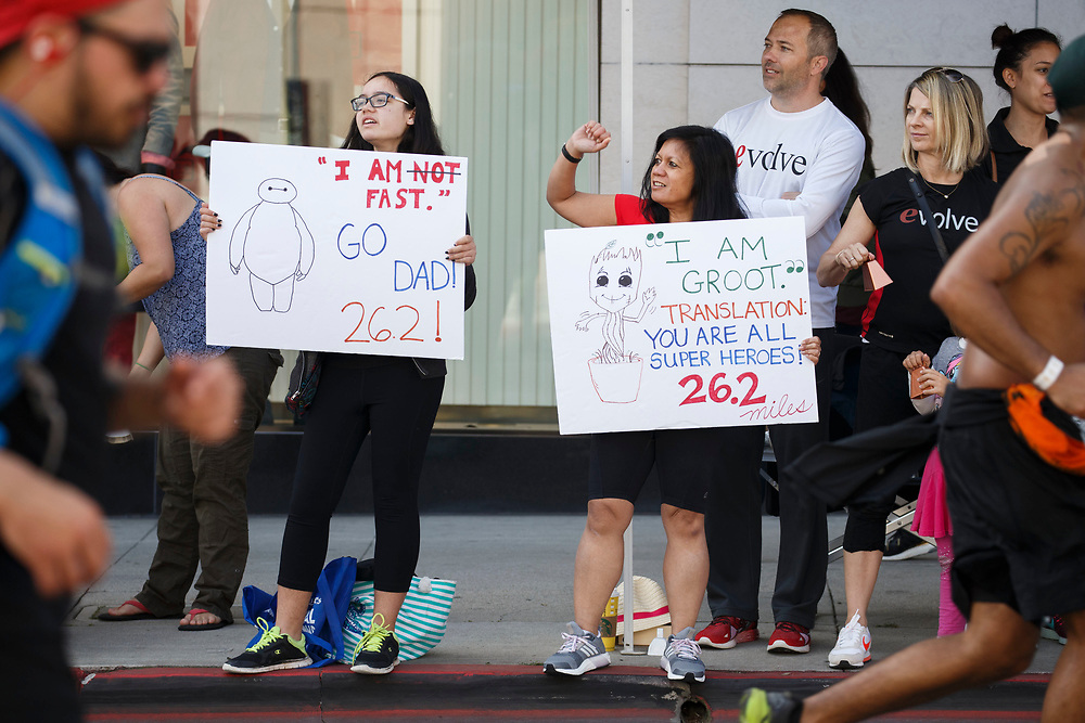 """Rio Hundley, 13, left and mom Jocelyn Julian, center, hold signs while waiting to cheer on dad near mile marker 17 during the 32nd annual Los Angeles Marathon on Sunday morning, March 19, 2017 in Beverly Hills, Calif.  The 26.2-mile """"Stadium to the Sea"""" route begins at Dodger Stadium and ends at Ocean and California avenues in Santa Monica. © 2017 Patrick T. Fallon"""