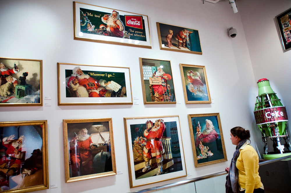 A visitor studying Haddon Sunblom's paintings of Santa Claus at The World of Coca Cola..The Santa Claus Haddon Sundblom created for Coca-Cola was used in advertisments meant to make people drink more Coca-Cola in the winter. Sundblom's image of Santa quickly became the standard for renditions of Santa Claus worldwide...The World of Coca-Cola is a permanent exhibition featuring the history of The Coca-Cola Company and its well-known advertising as well as a host of entertainment areas and attractions.