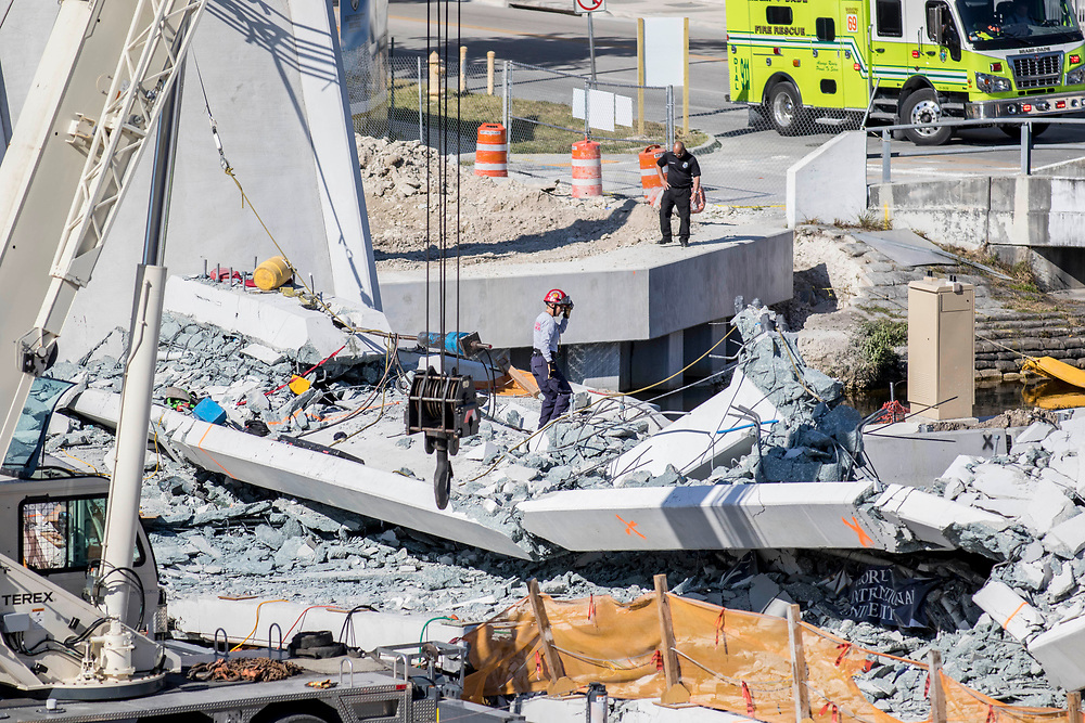First responders look for survivors among the debris created by the FIU bridge that collapsed Thursday afternoon leaving four people dead on March 15, 2018.<br /> <br /> photo by Samuel Navarro