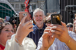© Licensed to London News Pictures. 30/06/2018. London, UK. Labour Party Leader JEREMY CORBYN (centre) poses for selfie photographs with protestors on Whitehall after a march in support of the National Health Service on the 70th anniversary of its founding. Thousands are taking part and will here speeches by Jeremy Corbyn and others in Whitehall. Photo credit: Rob Pinney/LNP