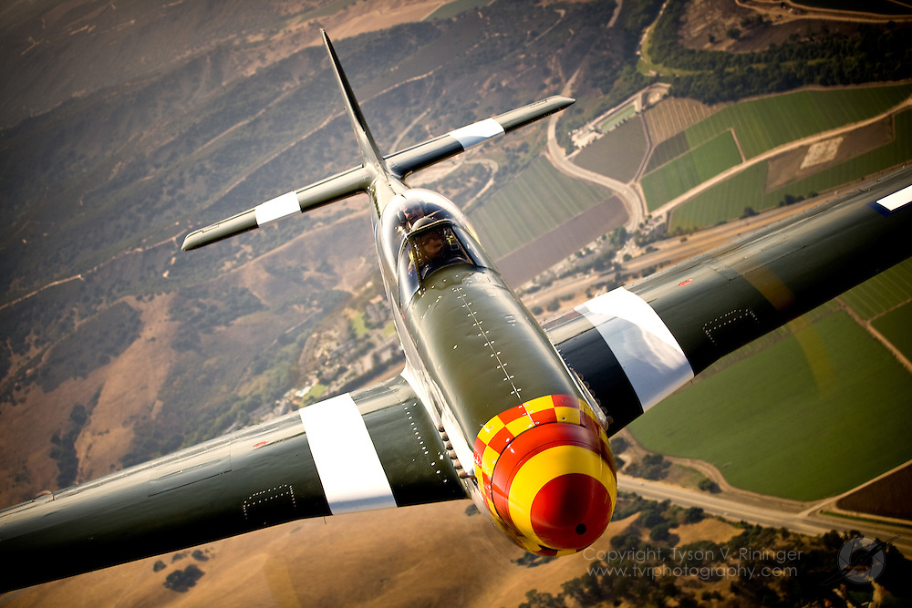 """A P-51D """"Wee Willy II"""" flown by Steve Hinton approaches the open ramp of a Rhode Island Air National Guard C-130J Hercules for a photoshoot in conjunction with the California International Airshow in Salinas."""