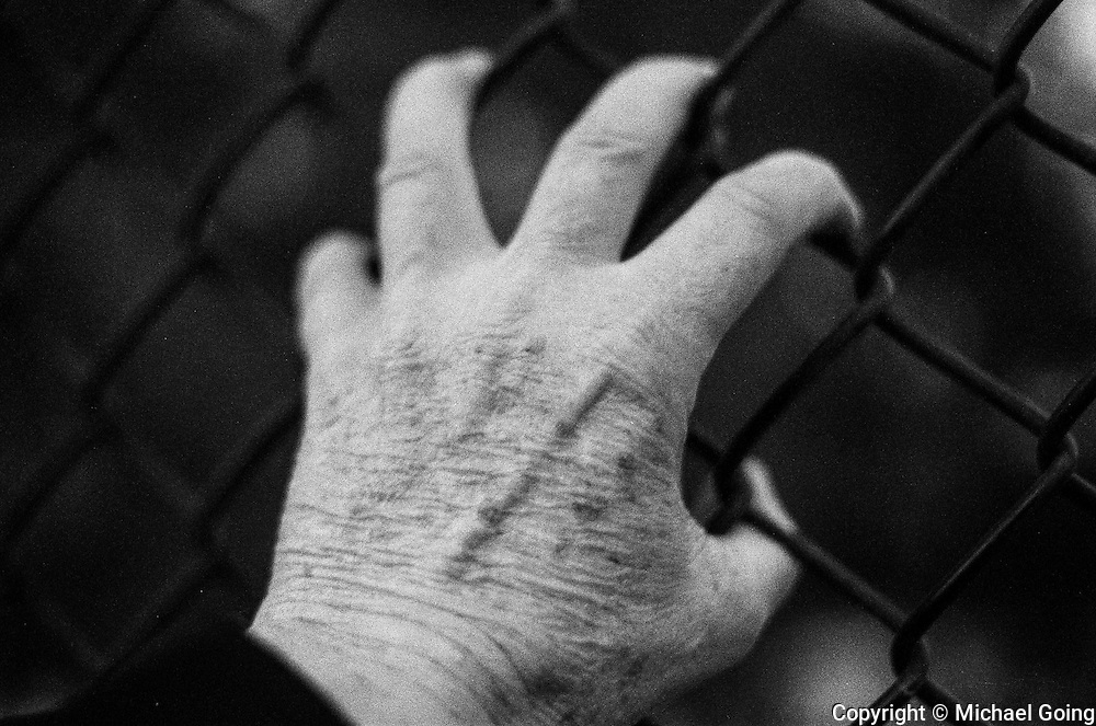 Black & white of close up on man's hand with fingers gripping chain link fence.