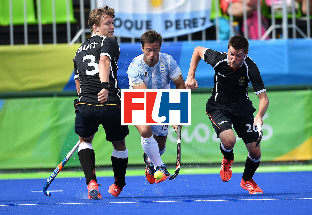 Germany's Linus Butt (L) and Martin Zwicker (R) chase Argentina's Juan Saladino during the men's field hockey Argentina vs Germany match of the Rio 2016 Olympics Games at the Olympic Hockey Centre in Rio de Janeiro on August, 11 2016. / AFP / MANAN VATSYAYANA        (Photo credit should read MANAN VATSYAYANA/AFP/Getty Images)