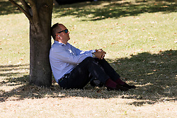 © Licensed to London News Pictures. 12/08/2016. LONDON, UK.  A man relaxes under a tree during the hot and sunny weather today in Green Park in London this lunchtime.  Photo credit: Vickie Flores/LNP