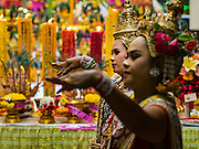 "21 DECEMBER 2015 - BANGKOK, THAILAND: Thai classical dancers perform during the annual rededication of a community Buddhist shrine in Pak Khlong Talat, also called the Flower Market. The market has been a Bangkok landmark for more than 50 years and is the largest wholesale flower market in Bangkok. A recent renovation resulted in many stalls being closed to make room for chain restaurants to attract tourists. Now Bangkok city officials are threatening to evict sidewalk vendors who line the outside of the market. Evicting the sidewalk vendors is a part of a citywide effort to ""clean up"" Bangkok.       PHOTO BY JACK KURTZ"