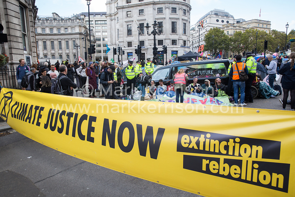 London, UK. 9 October, 2019. Climate activists from Extinction Rebellion blockade the Whitehall access to Trafalgar Square with a hearse on the third day of International Rebellion protests to demand a government declaration of a climate and ecological emergency, a commitment to halting biodiversity loss and net zero carbon emissions by 2025 and for the government to create and be led by the decisions of a Citizens' Assembly on climate and ecological justice.