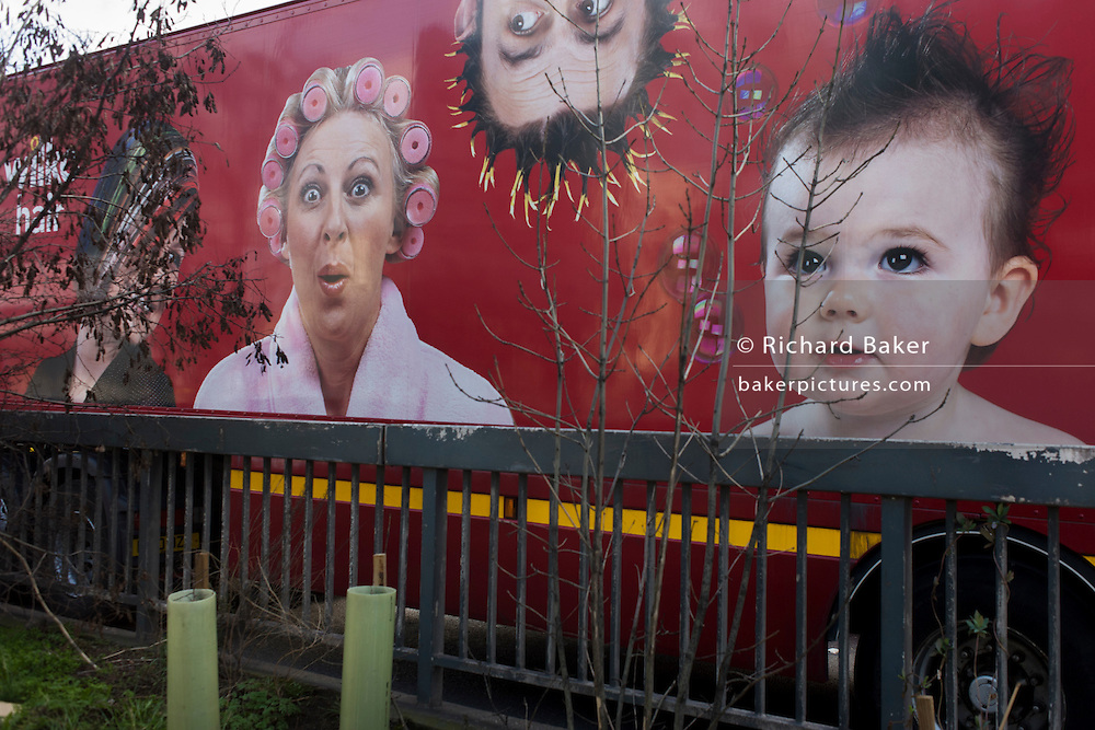 Faces of a family featured in a company ad on the side of a transport truck along with roadside wasteland railings.