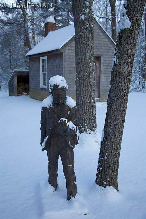 Sculpture of Henry David Thoreau in front of the replica of his cabin at Walden Pond, Massachusetts, covered in fresh snow.