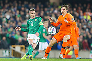 Northern Ireland midfielder Steven Davis (8) plays the ball as Netherlands midfielder Marten de Roon (15) tries to close him down during the UEFA European 2020 Qualifier match between Northern Ireland and Netherlands at National Football Stadium, Windsor Park, Northern Ireland on 16 November 2019.